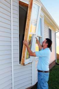 Professional window installer installing home windows.